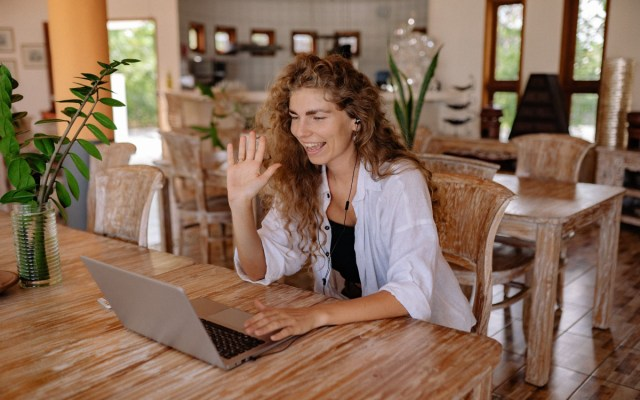 A person waving at their computer during a video call.