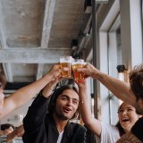 A group of friends cheers their beers over their table.
