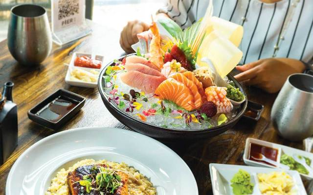 A large selection of sashimi samples is artfully filling up a bowl of ice, surrounded by flower petals.