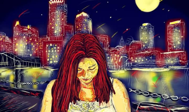 Na obrázku je červenovlasá žena v noci, stojící u řeky se sklopenou hlavou. Za řekou září město.