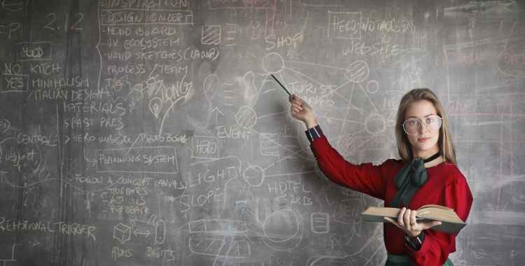 strict female teacher with book pointing at scribbled blackboard