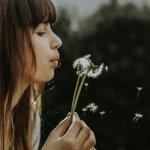 Eine junge Frau bläst in eine Pusteblume und die Samenschirmchen fliegen in die Welt