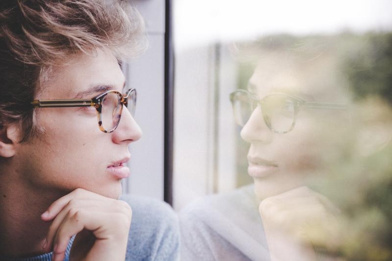 Selbstbild im Zugfenster - junger Mann betrachtet sich