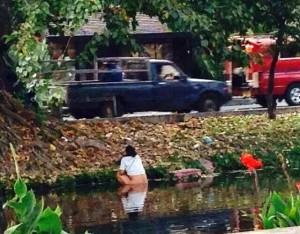 Chinese tourist in Chiang Mai taking a dump in the canal