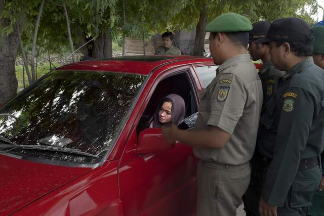 A woman and her husband, believed to be unmarried, are stopped and questioned by the religious police.