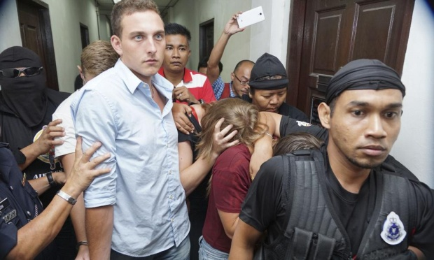Dutchman Dylan Snel, Briton Eleanor Hawkins (maroon top) and Canadian Danielle Petersen (black top) are escorted from court in Kota Kinabalu on Friday