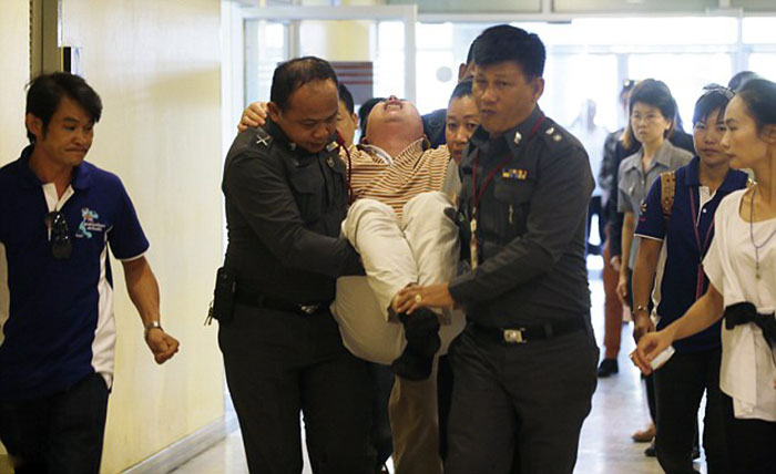 Torment: Gao Yan Ping, from Jiangxi province, China, is carried by police officers after arriving to claim the body and remains of his daughter and his wife who were killed in Monday's bombing at the Erawan Shrine