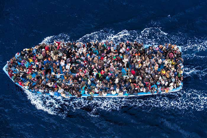 Hundreds of refugees and migrants aboard a fishing boat are pictured moments before being rescued by the Italian Navy as part of their Mare Nostrum operation in June 2014. Among recent and highly visible consequences of conflicts around the world, and the suffering they have caused, has been a dramatic growth in the number of refugees seeking safety by undertaking dangerous sea journeys, including on the Mediterranean.