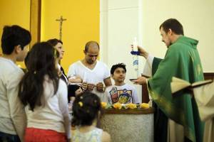 Pastor Gottfried Martens lights a candle during a service to baptise migrants from Iran at the Trinity Church in Berlin. Pictured third right is Mohammed Ali Zanoobi who is among hundreds of mostly Iranian and Afghan asylum seekers who have converted to Christianity at the evangelical church in a leafy Berlin neighborhood