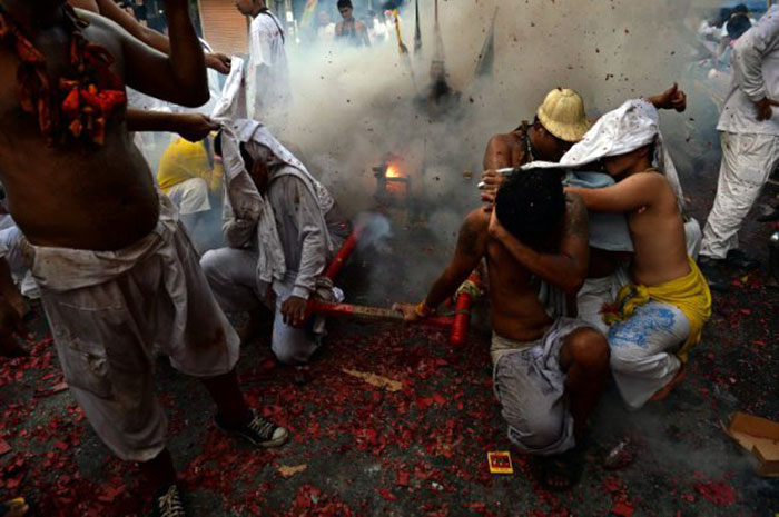 Devotees-protect-themselves-as-firecrackers-explode-near-an-idol-they-carry-on-a-palanquin-during-a-street-procession-during-the-annual-Vegetarian-Festival-in-Phuket