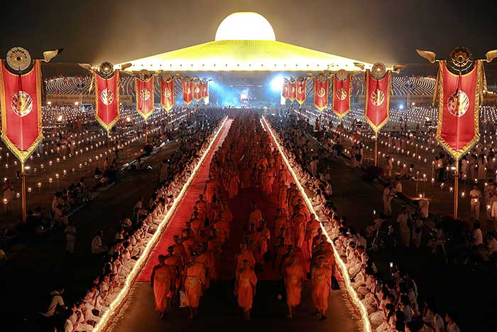 Buddhist-monks-walk-between-two-rows-of-candles-at-the-Wat-Phra-Dhammakaya-temple-in-Pathum-Thani-province
