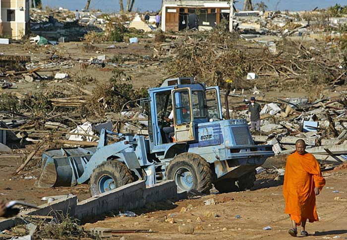 A Thai Buddhist monk passes a bulldozer as it clears debris from what used to be a hotel resort in Khao Lak in Southern Thailand on Thursday, Dec. 30, 2004. Officials say more than 6,000 Thais and foreigners are missing, while 1,975 are confirmed to have perished in Sunday's tsunami disaster. (AP Photo/Richard Vogel)