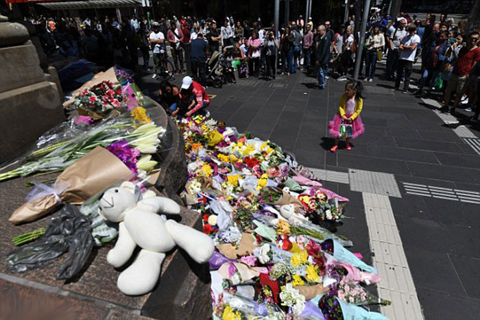 a-little-girl-is-pictured-contributing-to-the-growing-floral-tribute-in-melbournes-centre-on-saturday