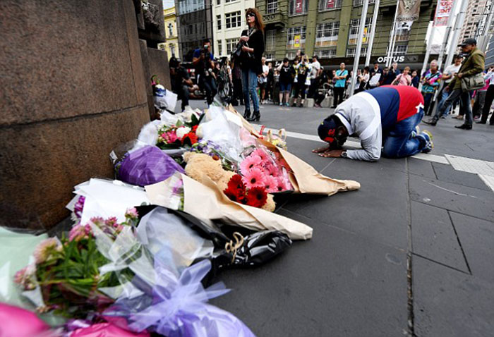 a-mourner-prays-where-flowers-are-being-laid-on-the-corner-of-bourke-and-elizabeth-street-in-melbourne
