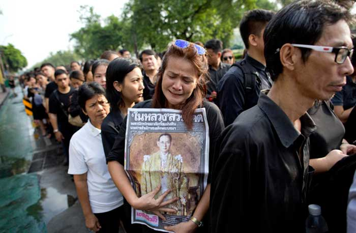 A Thai woman weeps as she holds on to a portrait of Thai King Bhumibol Adulyadej in a line to offer condolences for the king at Grand Palace in Bangkok, Thailand, Friday, Oct. 14, 2016. Grieving Thais went to work dressed mostly in black Friday morning, just hours after the palace announced the death of their beloved King Bhumibol, the politically fractious country's unifying figure and the world's longest-reigning monarch