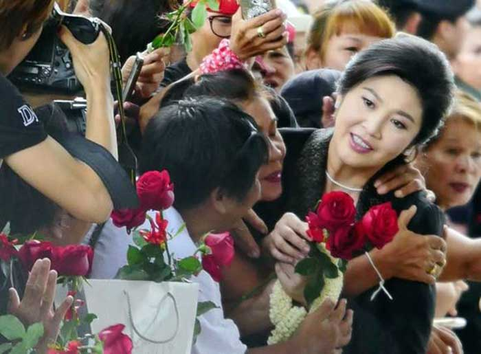 Ousted former Thai prime minister Yingluck Shinawatra greets supporters as she arrives at the Supreme Court in Bangkok on August 1.