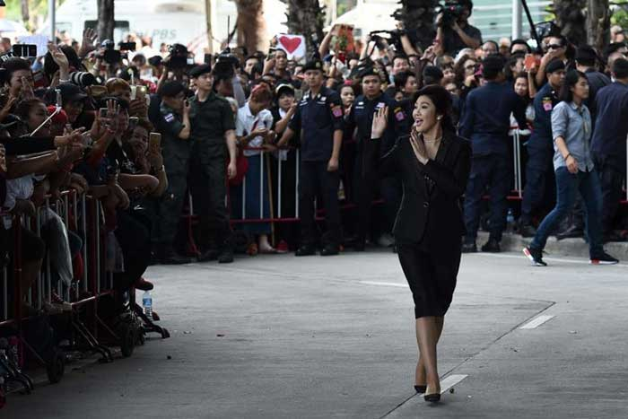 Ousted former Thai prime minister Yingluck Shinawatra greets supporters as she arrives at the Supreme Court in Bangkok on August