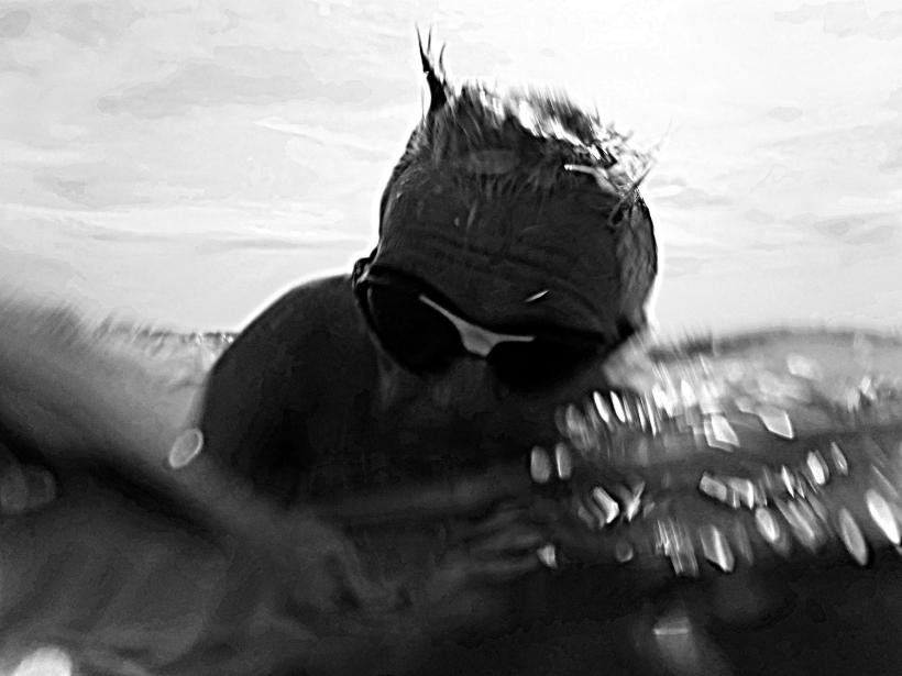 Foto in schwarz/weiß: In der Brandung des Meeres, mit Schwimmbrille, gewollt unscharf