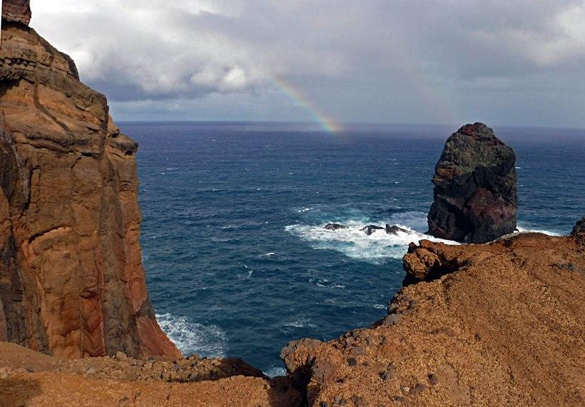 Reisefotos: Rote Lavafelsen über dem Meer. Ein Regenbogen im Hintergrund