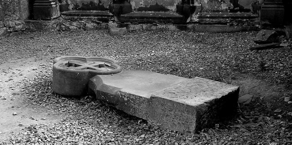 Foto in schwarz/weiß: Ein umgestürzter Grabstein mit einem Kreuz oben.