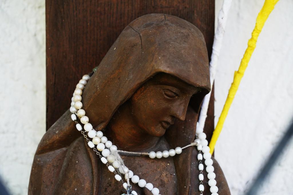 Frau unter dem Kreuz mit Rosenkranz