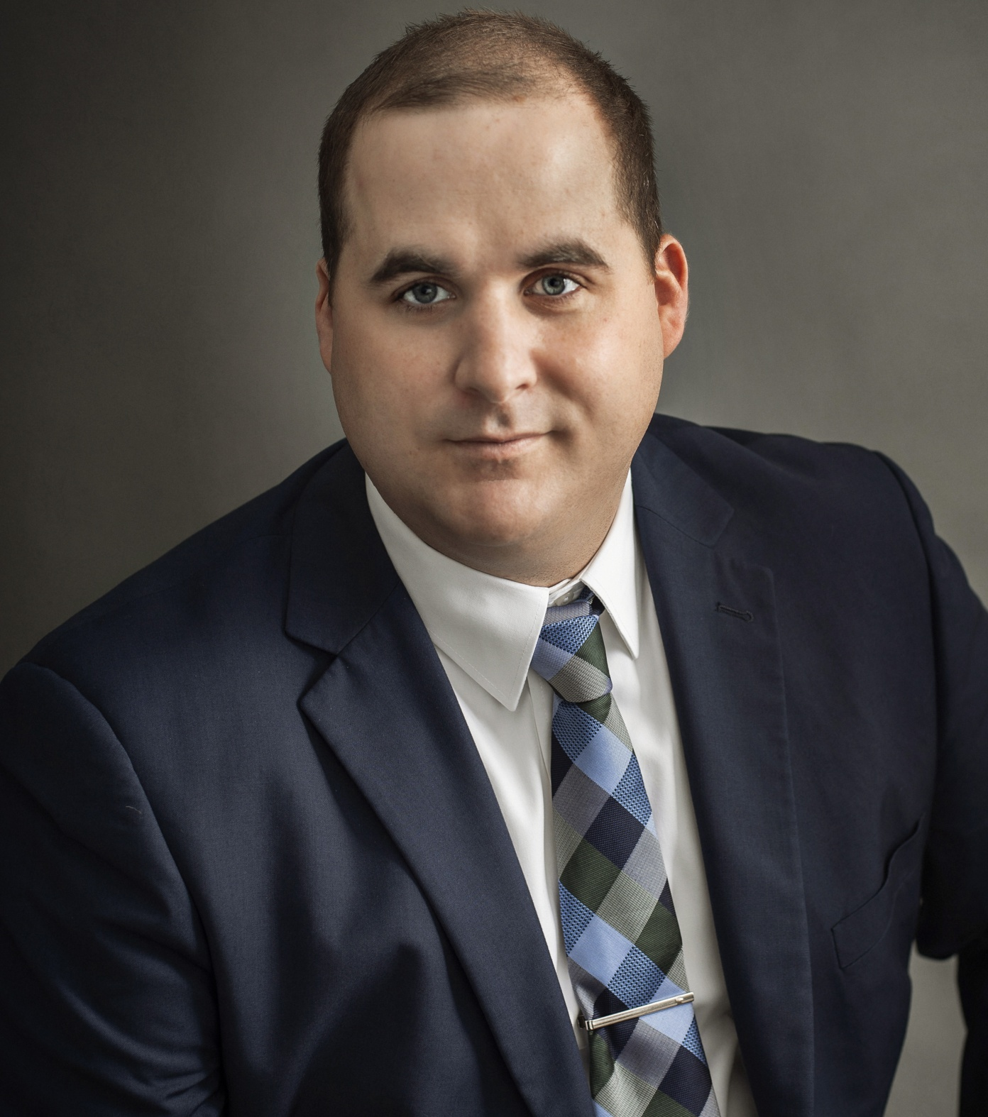 Headshot of Gregory D. Sobol, Esp. He is wearing a navy suit and blue & green square patterned tie over a white button-up shirt. He has a light, amiable expression.