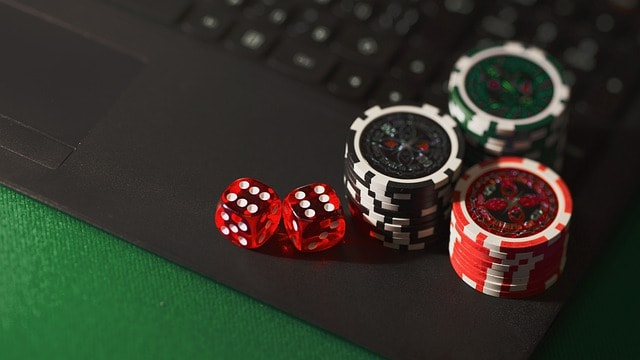 poker chips and dice on a laptop